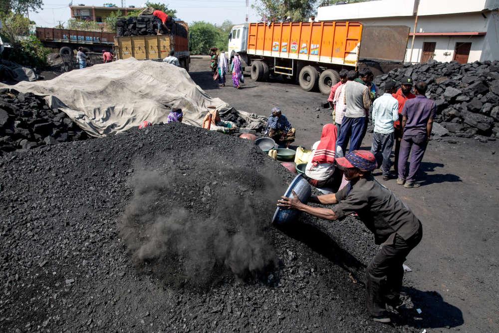 Sur la route desservant les mines de Padmapur et Durgapur, des manoeuvres vident des camions à la main, sur une aire de stockage. Le charbon est ensuite vendu aux briqueteries, cimenteries et aciéries de la région.