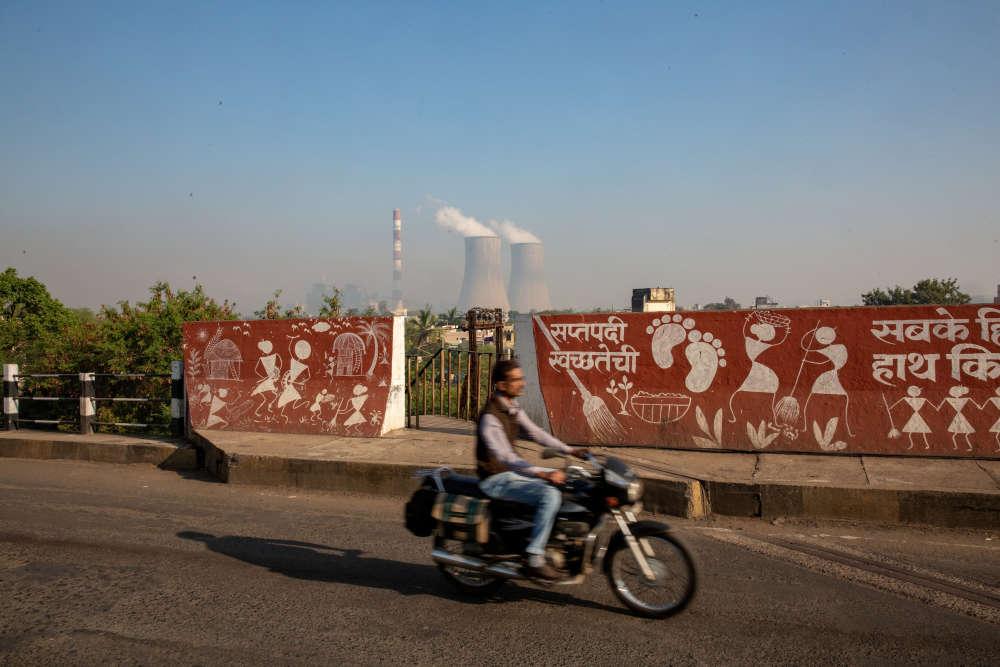 Les campagnes publicitaires pour une Inde plus propre recouvrent souvent les murs des villes, comme ici à Chandrapur, alors qu'au loin, la centrale à charbon, aux allures de centrale nucléaire avec ses deux tours de refroidissement, rejette des cendres dans l'atmosphère par sa grande cheminée rayée.