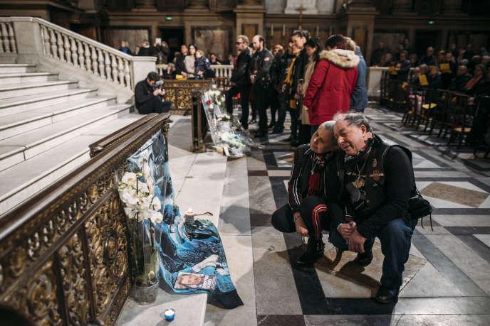 Des fans se recueillent devant des photos à l'effigie de leur idole, avant la messe en hommage à Johnny à l'église de la Madeleine, à Paris, le 9 février.