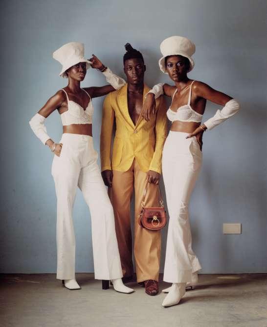 De gauche à droite,boots en cuir, Balenciaga. Bracelets en métal, Chloé. Costume en nylon, Ermenegildo Zegna. Pantalon en coton, Telfar. Sac en cuir verni, Chloé. Chaussures en velours et cuir verni, Gucci.