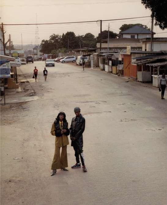 De gauche à droite, costume trois-pièces en laine et fausse fourrure, Ibkamarastudios. Bottines en cuir imprimé python, Dorateymur. Veste et pantalon en cuir, baskets en tissu et caoutchouc, Lanvin. Casquette en laine, Haos Studio.Assistant Photographe: Tot Man — Assistant Styliste : Sasha Harris — Maquillage : Ammy Drammah — Coiffure : Mamoud Hamid Vijay, avec Bernice Sefakor Buo — Production : Rhoda Kokoroko, avec Emily Tetteh-Quaye, Benet Obeng, Deladem Barrigah, Raymond Baffour — Remerciements à Joseph Bates, Seyon, et aux habitants d'Accra.