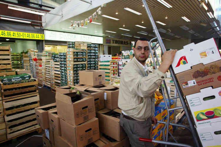 Un employé transporte des cageots de fruits, le 29 juillet 2003, dans le secteur des fruits et légumes, lors de la première visite du ministre de l'agriculture, Hervé Gaymard, au marché de Rungis.