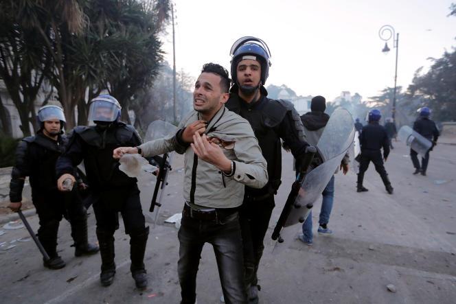 Un policier retient un manifestant, le 1er mars à Alger.