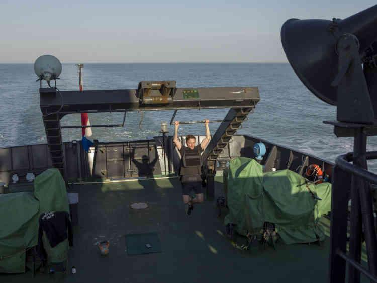 Justin, un des matelots, fait du sport à la poupe du bateau.