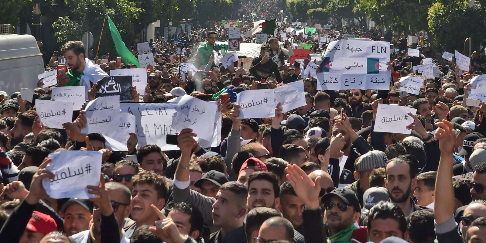 Algerians march with protest sings reading