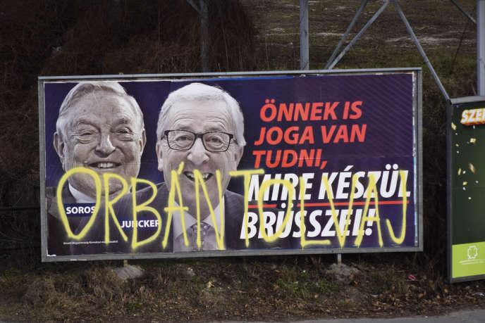 Une affiche du gouvernement contre le milliardaire George Soros et le président de la Commission européenne, Jean-Claude Juncker, taguée « Orban, bandit », à Budapest, le 26 février. Pablo Gorondi/AP