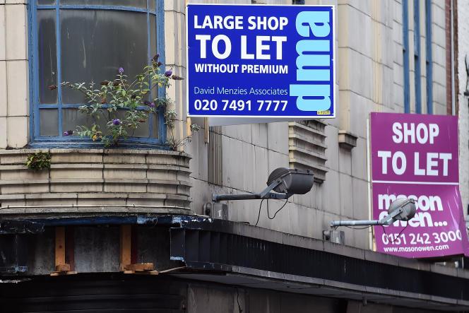 Des affiches indiquant des locaux commerciaux disponibles à la vente à Liverpool, Royaume-Uni, le 17 août 2016.