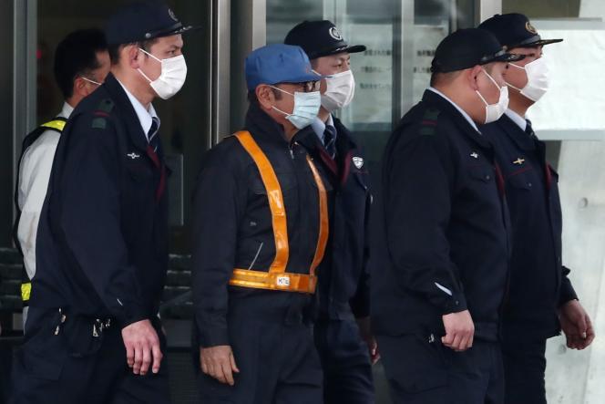 Carlos Ghosnétait escorté par de policiers, et portait une casquette et un masque facial.