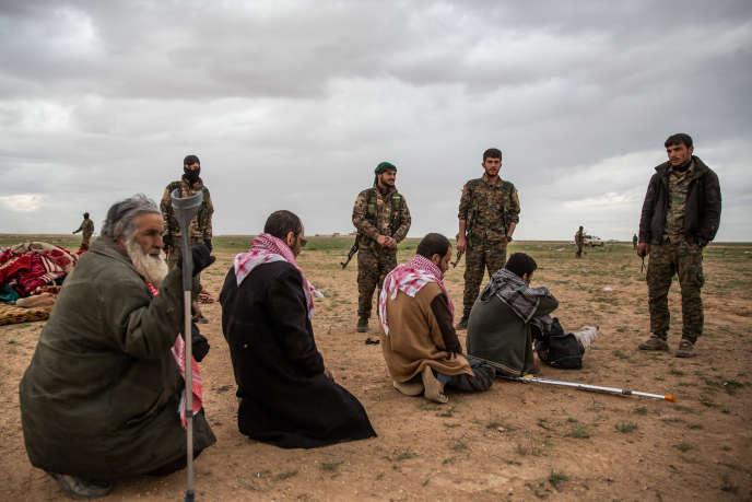 Sur le campement de Tanak, le 27 février, des civils fuyant Baghouz, la dernière poche encore tenue par l'Etat islamique, sont fouillés par les Forces démocratiques syriennes.