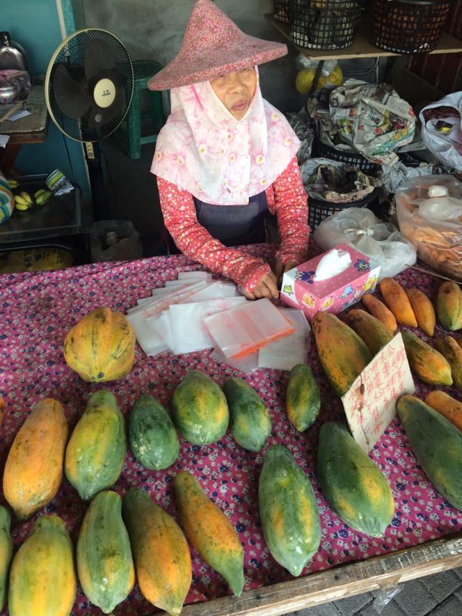 Vendeuse de papayes et sa coiffe traditionnelle, à Tainan.