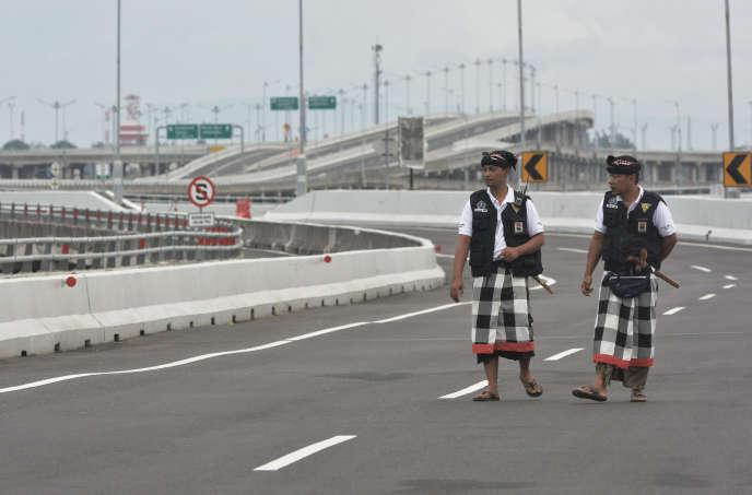 Des agents de sécurité marchent sur une autoroute vidée de ses voitures, jeudi 7 mars, jour de Nyepi.