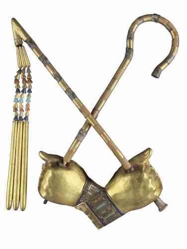 «Lorsque le Britannique Howard Carter ouvrit le dernier cercueil du jeune roi, en 1922, il découvrit la momie parée de divers bijoux et ornements en or, incrustés pour certains de verre et de pierres semi-précieuses. L'envers des bandes maintenant le linceul sur le corps révèle qu'une partie de ces ornements avaient, à l'origine, été réalisés pour une reine-pharaon qui précéda Toutankhamon sur le trône d'Egypte. Comme sur les trois cercueils-gigognes enfermant la momie, la position croisée des mains, de même que le sceptre heqa et le fouet nekhekh identifient Toutankhamon au dieu Osiris, souverain de l'au-delà.»