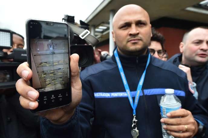 Un surveillant montre une photo des objets prohibés trouvés dans l'année dans des cellules de la prison de Condé-sur-Sarthe (Orne), le 6 mars.
