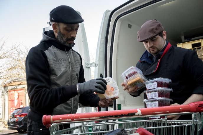 Yoka, un chauffeur bénévole chez Les Restos du cœur, vérifie avec un employé d'un supermarché les dates d'expiration des produits avant de les ramener pour le tri et la distribution.