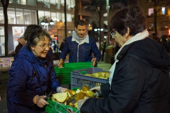 Des bénévoles des Restaurants du cœur préparent la distribution du soir sur la place de Budapest, près de Saint-Lazare, à Paris, le 27février.