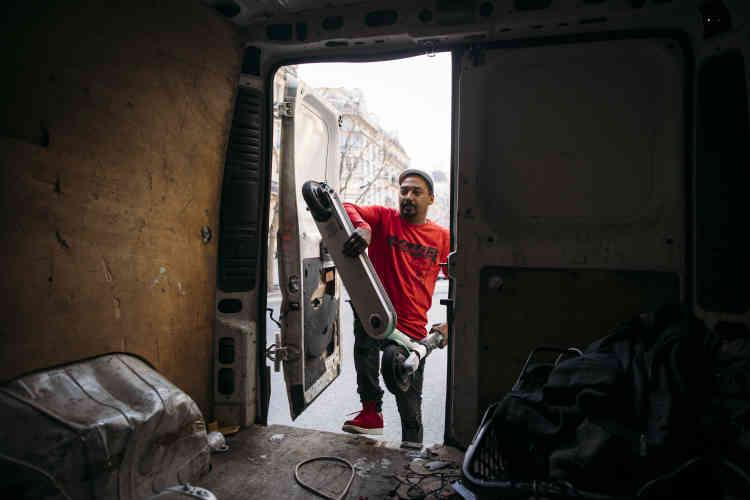 Les trottinettes sont chargées à l'arrière de son camion.