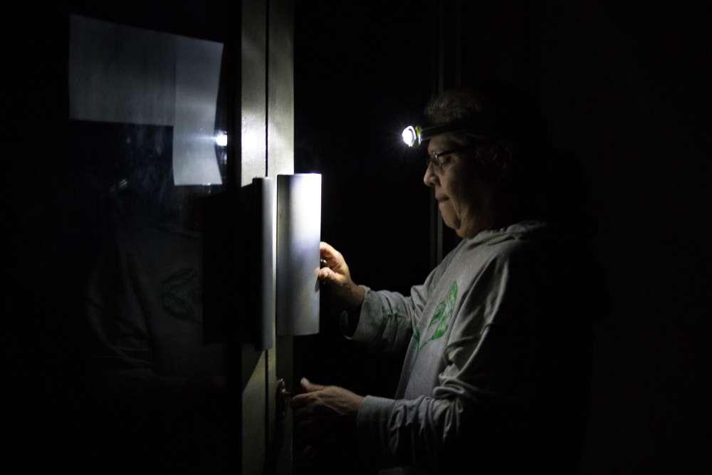 Lampe au front, un homme tente de rentrer dans un immeuble, le 9 mars à Caracas.