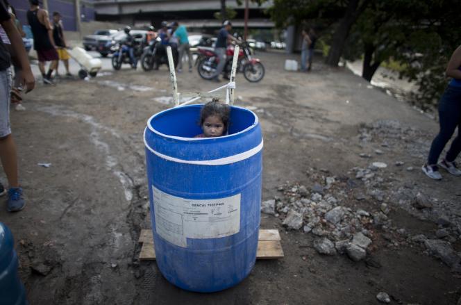 Une petite fille dans un tonneau en plastique tandis que sa famille attend pour collecter de l'eau, dans une rue de Caracas, le 11 mars.