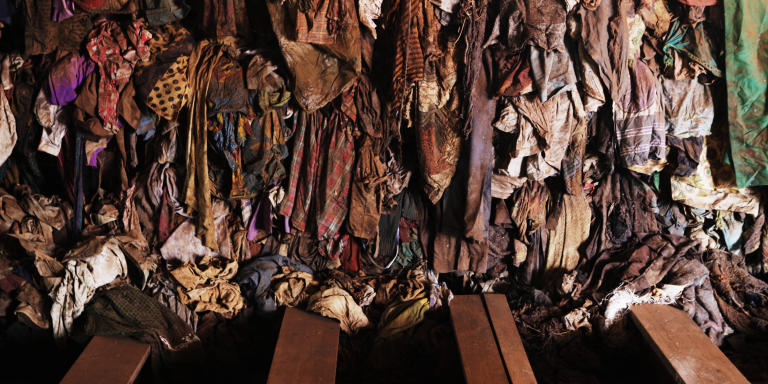 Bloodied and dust-covered clothing from Rwandan victims hang from a wall at a genocide memorial inside the church at Ntarama just outside the capital Kigali, August 6, 2010. Some 5,000 people, mostly women and children, sought refuge near the church in April 1994, but were massacred by Hutu extremists who used grenades, clubs and machetes to kill their victims. Rwandan voters go to the polls on Monday for the second presidential election since the genocide 16 years ago. REUTERS/Finbarr O'Reilly (RWANDA - Tags: POLITICS ELECTIONS CONFLICT) - GM1E6861D0I01