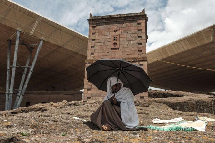 Un etiopico ortodosso ripara dal sole tra due chiese a Lalibela coperte da tetti protettivi, 6 2019 di marzo.