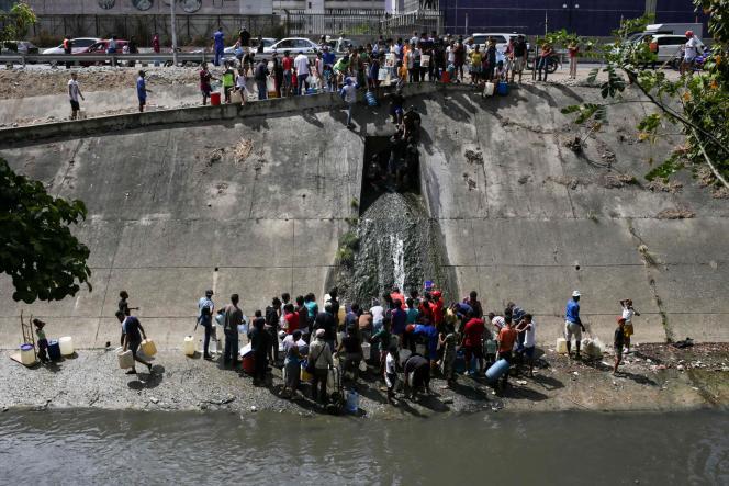 Des habitants collectent des eaux usées d'un canal à Caracas, le 11 mars.
