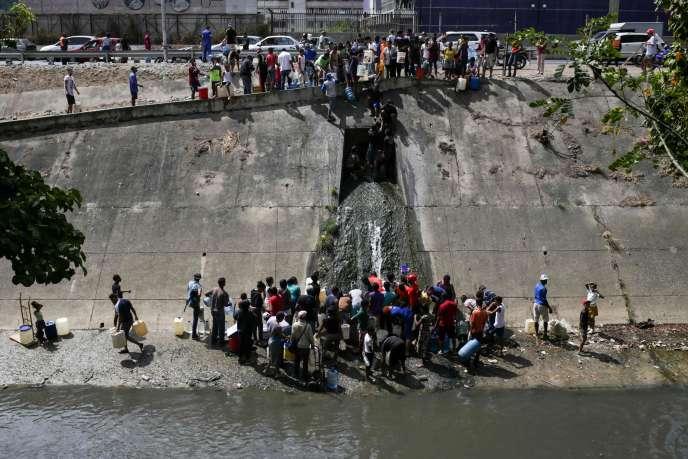 Des habitants de Caracas recueillent l'eau d'un canal d'égout à la rivière Guaire, le 11mars2019.