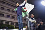 TOPSHOT - An Algerian stands with a national flag during a demonstration in the centre of the capital Algiers on March 11, 2019, after President Abdelaziz Bouteflika announced his withdrawal from a bid to win another term in office and postponed an April 18 election, following weeks of protests against his candidacy.  Bouteflika, in a message carried by national news agency APS, said the presidential poll would follow a national conference on political and constitutional reform to be drawn up by the end of 2019. / AFP / RYAD KRAMDI