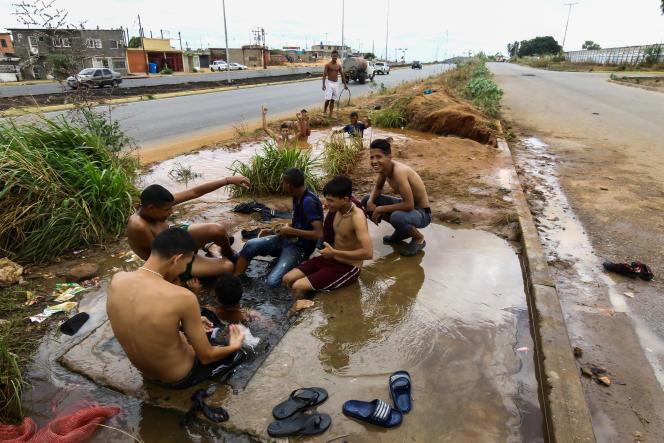 Des gens se lavent dans la rue grâce à une canalisation percée, à San Felix, le 12 mars.