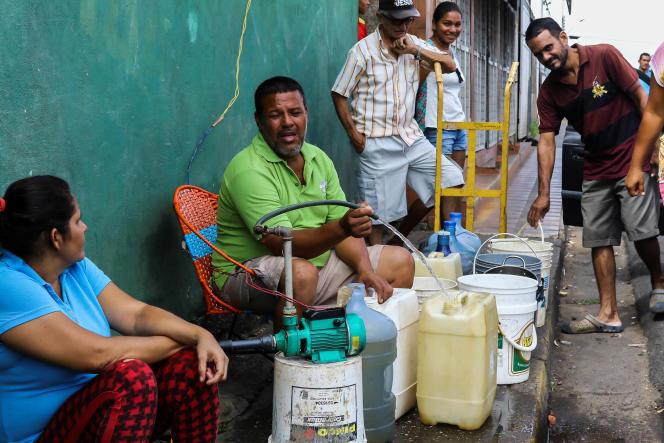 Des Vénézuéliens se regroupent autour des alimentations d'eau pour remplir des bidons. Le 12 mars 2019 à San Felix.