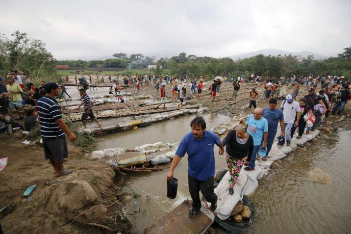 Des Vénézuéliens quittant le pays, en passant la rivière Tachira à la frontière avec la Colombie, le 12 mars 2019.
