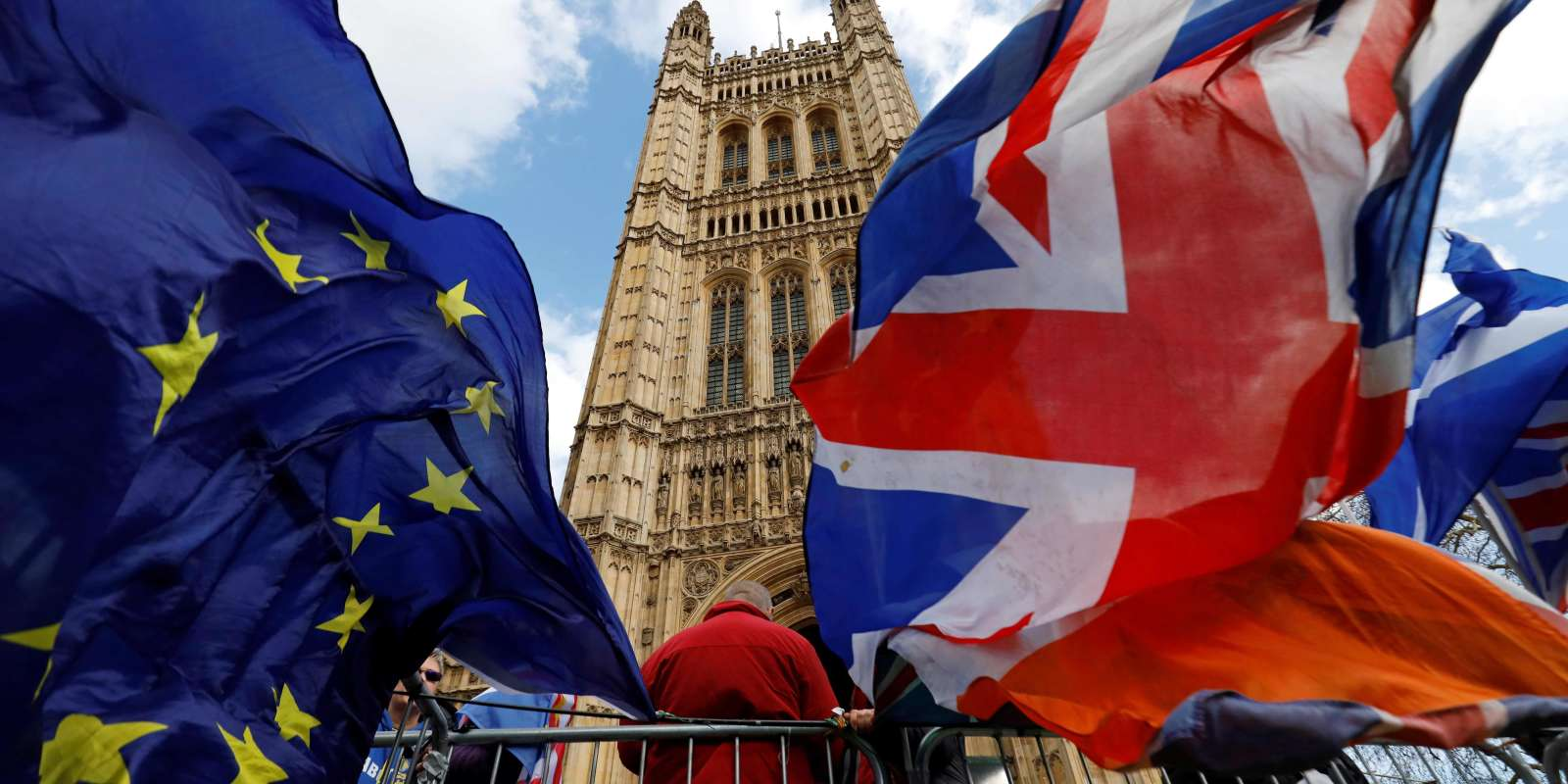 Pro-Brexit and anti-Brexit protesters hold flags as they demonstrate outside the Houses of Parliament in London on March 14, 2019 as members debate a motion on whether to seek a delay to Britain's exit from the EU. MPs vote on March 14 on whether to seek a Brexit delay, as the chaotic process to end Britain's 46-year membership of the EU plunges the country into deep political crisis. / AFP / Tolga AKMEN