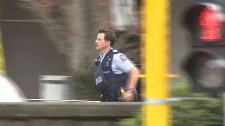 Un policier se précipite sur le lieu d'une attaque survenue à Christchurch, en Nouvelle-Zélande, vendredi 15 mars. Des fusillades contre deux mosquées ont fait au moins 49 morts.