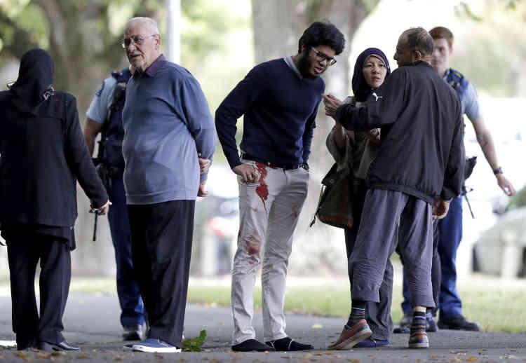 Des témoins près du lieu de l'attaque, à Christchurch. Trois personnes ont été placées en garde à vue. Un tireur a été identifié comme un extrémiste de droite australien.