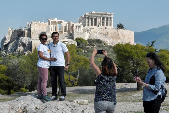 Des touristes se prennent en photo devant l'Acropole d'Athènes, en octobre 2018.