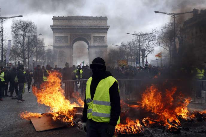 Un manifestant devant une barricade, Paris, le 16 mars 2019.