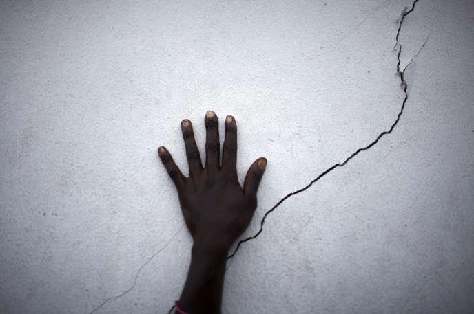 Une femme pose sa main sur une fissure située sur le mur d'une banque alimentaire en Haïti, le 27 janvier 2010.