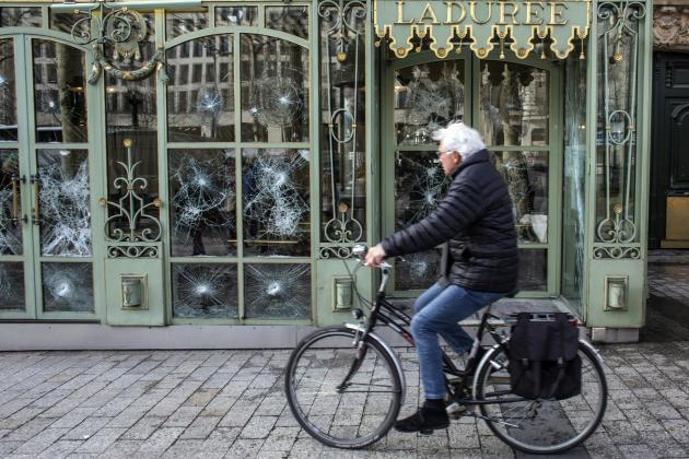 Un cycliste passe devant les fenêtre brisées du salon de thé Ladurée sur les Champs-Elysées.