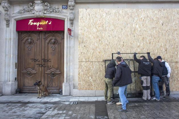 Des ouvriers fixent des planches protectrices sur la façade du Fouquet's, le 17mars.