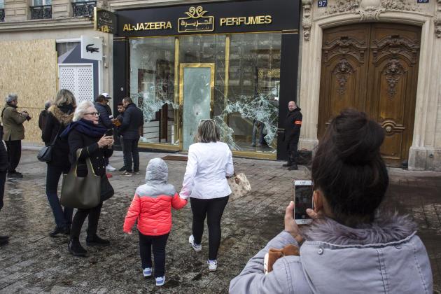 Des passants photographient une parfumerie vandalisée, dimanche17 mars, sur les Champs-Elysées.