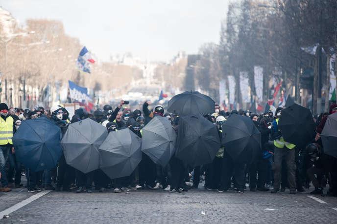 Des manifestants avancent abrités par des parapluies, le 16mars à Paris.