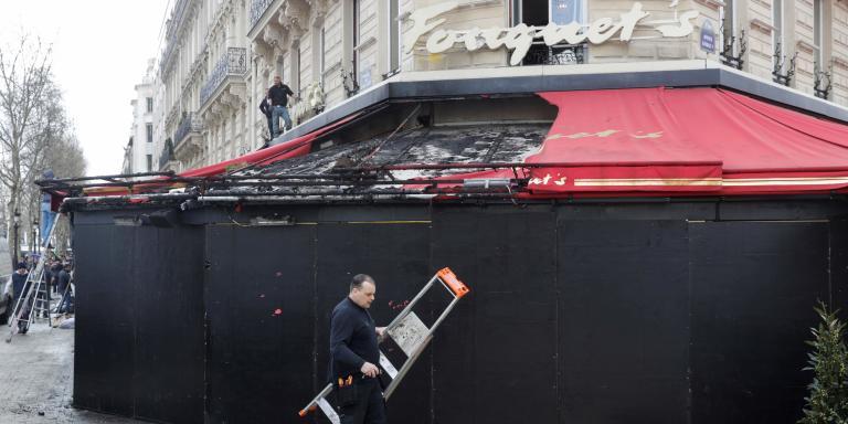 Men work on damages of the restaurant