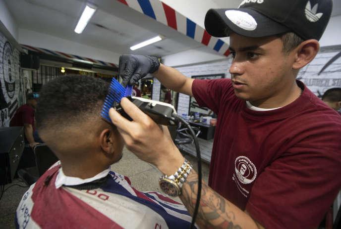 Jorge Gil, un réfugié vénézuélien, travaille dans un salon de coiffure de Lima, en janvier. Tous les employés de l'établissement sont des Vénézuéliens.