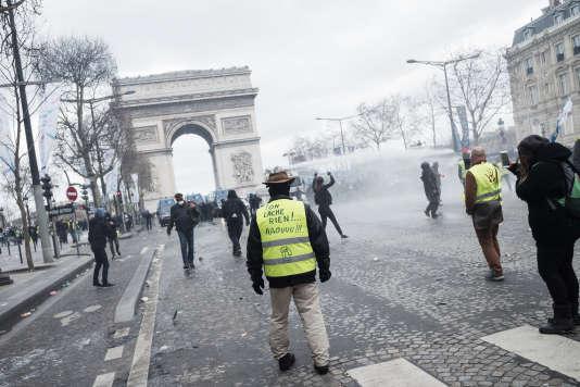 """Avenue des Champs-Elysées, à Paris, le 16 mars, lors de l'acte XVIII des« gilets jaunes».Un manifestant porte sur son gilet l'inscription«on lâche rien !…aaouuu!""""."""