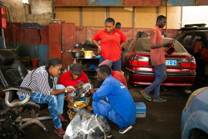 En banlieue de Dakar, l'équipe du garage Femme Auto, à parité femmes-hommes, déjeune ensemble.