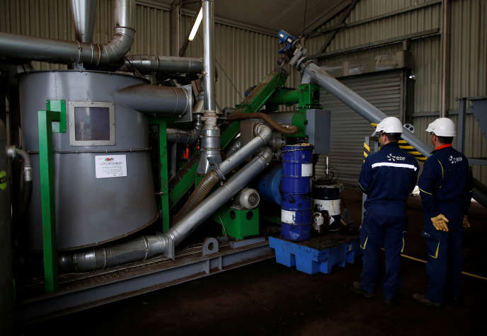 Des salariés d'Electricite de France, près d'un prototype de four à pellets, des granulés fabriqués à base de déchets debois, permettant de réduire la consommation de charbon. Le 21 mars, à Cordemais.
