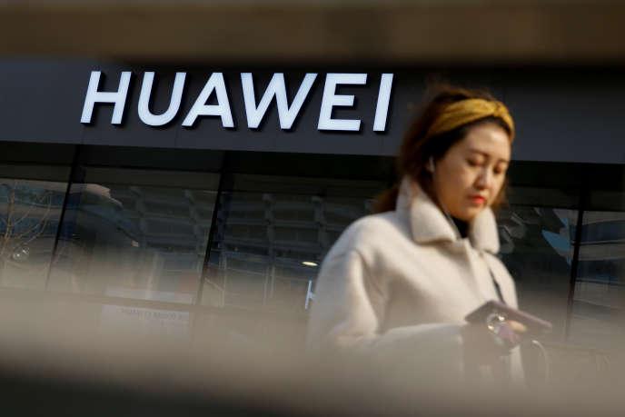 Une femme passe devant une boutique Huawei à Pékin, le 29 janvier.
