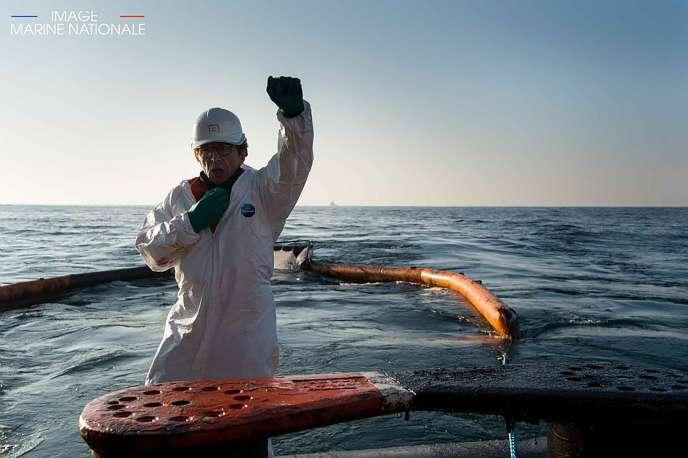Cette photo prise et publiée par la marine nationale le 22 mars 2019 montre un ouvrier en train d'installer un barrage pétrolier sur le navire BSAA «Argonaute» après l'incendie et le naufrage du cargo italien «Grande-America» dans le golfe de Gascogne.