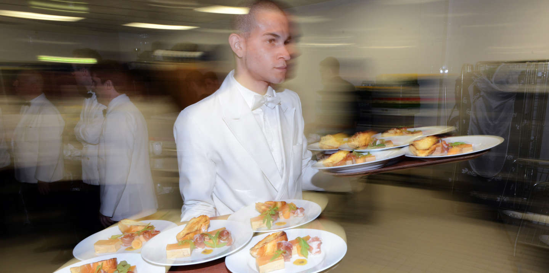 Des serveurs receptionnent les plats à servir à l'occasion d'une réception d'un grand restaurant