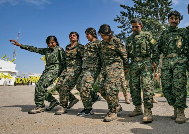 Des combattants des Forces démocratiques syriennes (FDS) fêtent la chute de l'EIdans le village de Baghouz, le 23 mars.