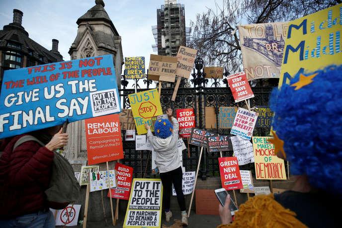 Des manifestants proeuropéens posent des pancartes sur les grilles du Parlement britannique, à Londres, le 23 mars.